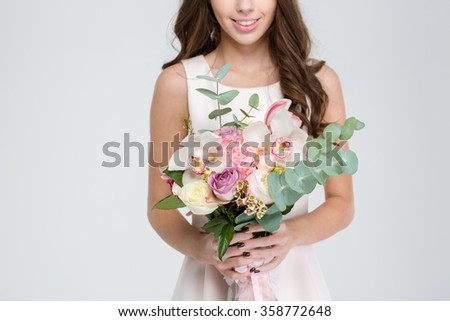 Close up of beautiful bouquet of flowers holded by cheerful young woman in white dress over white background - stock photo