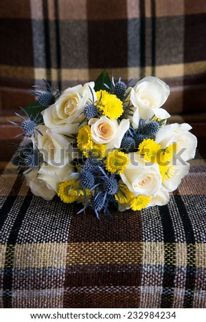 Close up of beautiful bridal bouquet on vintage, upholstered chair at Muskoka cottage wedding - stock photo