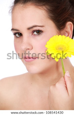 Close up of beautiful brunette woman enjoying a day at the spa with yellow aromatic Gerber flower isolated on white background - stock photo