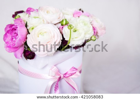 close up of beautiful bunch of summer flowers in round cardboard box over white background