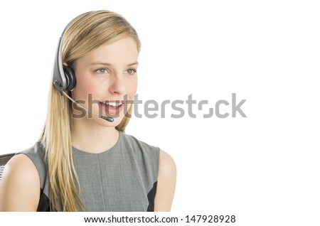 Close-up of beautiful customer service representative wearing headset looking away against white background - stock photo