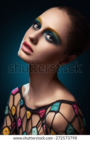 Close-up of beautiful female face with colorful make-up.Beauty. Fresh glowing skin. Accessory.Flower.Blue.Art.Theater.Face art.Bright.Closeup.Portrait.Look Fashion make-up. Fantastic Modern production - stock photo