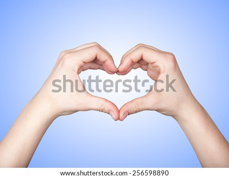 Close up of beautiful female hands form heart shape isolated on blue background