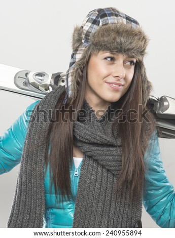 close up of  beautiful female skier with ski on her back. shot  in studio on gray background. - stock photo