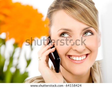 Close-up of beautiful female smiling and talking on cell phone, looking up - stock photo