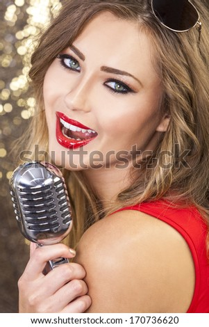 Close up of beautiful female woman singer mouth with red lips singing into a vintage microphone in a night club