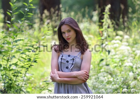 Close-up of beautiful girl in dress and long hair with view of forest in background with shallow depth of field - stock photo