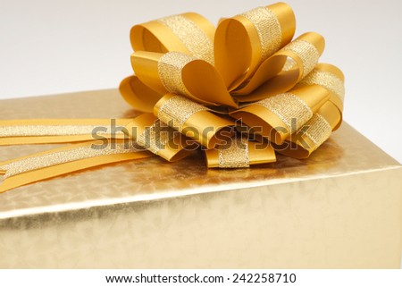 Close up of beautiful golden gift box or present for giving to love one on special occasion - stock photo