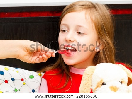 Close up of beautiful little girl taking her syrup as treatment. - stock photo