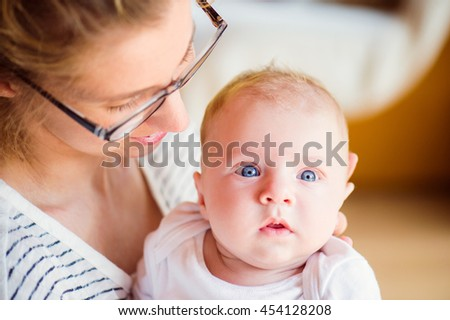 Close up of beautiful mother holding her baby son - stock photo