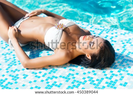 Close-up of beautiful, sexy, sporty girl in alluring swimwear lying poolside.