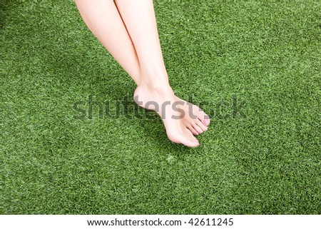 Close up of beautiful slim female feet on green grass