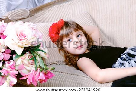 Close-up of Beautiful small girl lying on sofa near flowers  - stock photo