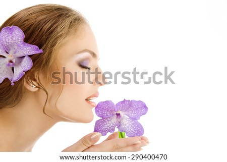 Close-up of beautiful tender female profile with violet orchids at the white background. - stock photo