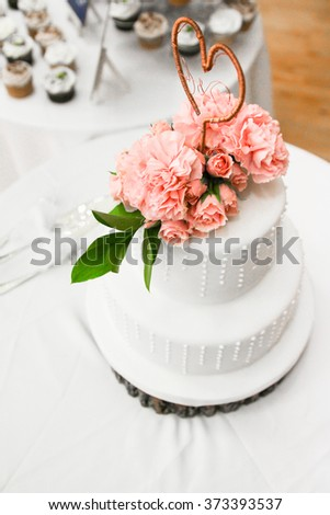 Close Up Of Beautiful Three Layered American White Wedding Cake Idea On Wood Basing With Heart Attached, Pink Roses, & Green Leaves At Wedding Reception Occasion