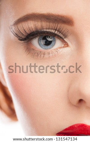Close-up of beautiful woman blue eye with long lashes and bright makeup - stock photo