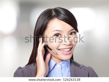 close up of beautiful woman customer support operator with headset and smiling at office, asian woman - stock photo
