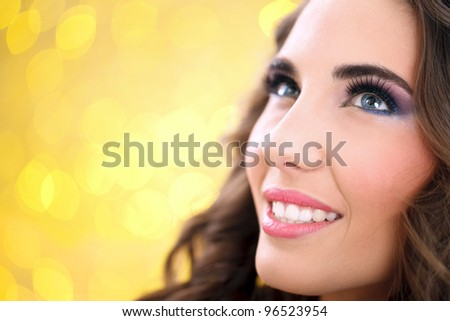close up of beautiful woman face over yellow background