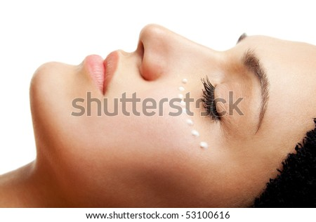 Close-up of beautiful woman face receiving an eye cream treatment - stock photo