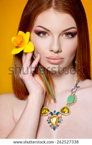 Close-up of beautiful woman face with colorful make-up and lips with flower - stock photo