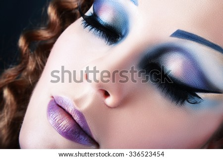 Close-up of beautiful woman face with Creative Fashion Art make up and eyelashes. Studio - stock photo