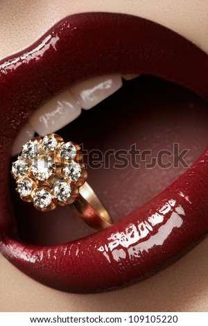 Close-up of beautiful woman's lips with bright fashion dark red glossy makeup. Macro lipgloss cherry make-up. Mouth with wedding gold diamond ring. Jewelry accessories. - stock photo