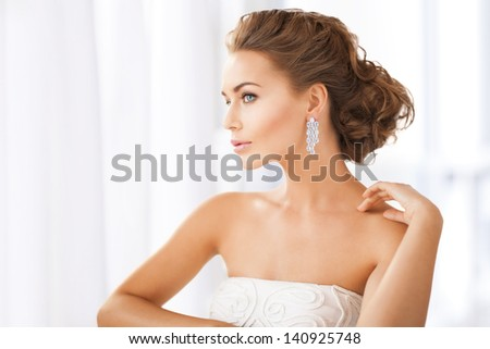 close up of beautiful woman wearing shiny diamond earrings - stock photo