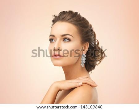 close up of beautiful woman wearing shiny diamond earrings - stock photo