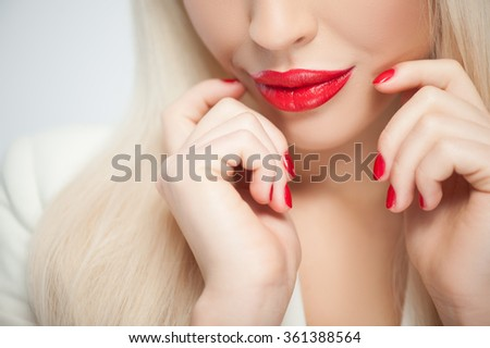 Close up of beautiful woman with red sexy lips, manicure and blond wig. She is touching her face gently and smiling - stock photo