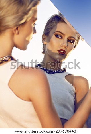 Close up of beautiful young  blonde woman looking on her-self thought mirror. Wearing white vest and necklace. Her hair is tied to ponytail. Professional make-up, hair style and styling. - stock photo