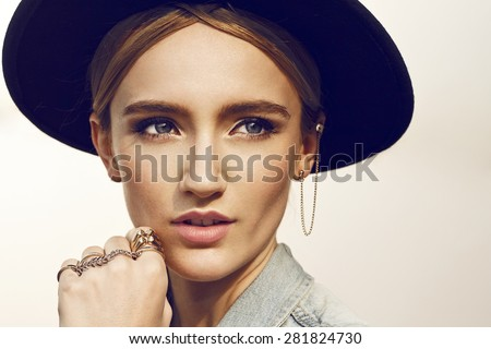 Close up of beautiful young  blonde woman with black hat. Wearing denim vest. Her hair is tied to ponytail. Professional make-up, hair style and styling. - stock photo