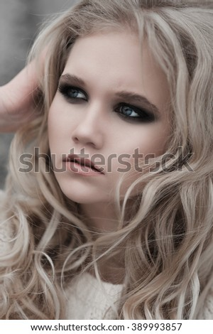Close up of beautiful young  blonde woman with blue eyes in white pullover.  Winter, spring, outdoor portrait. Professional beauty make-up: dark smoky eyes and pale lips and hair style. Retouch.