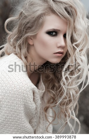 Close up of beautiful young  blonde woman with blue eyes in white pullover.  Winter, spring, outdoor portrait. Professional beauty make-up: dark smoky eyes and pale lips and hair style. Retouch. - stock photo