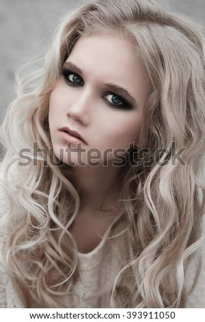 Close up of beautiful young  blonde woman with blue eyes in white pullover.  Winter, spring, outdoor portrait. Professional beauty make-up: dark smoky eyes and pale lips and hair style.