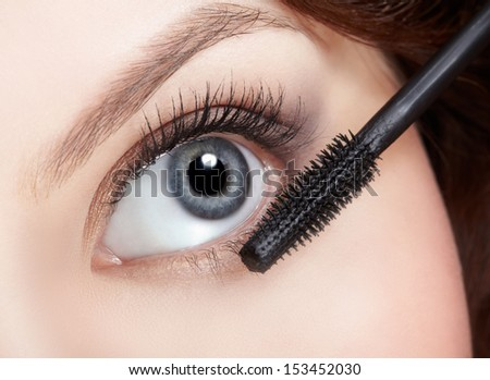 close-up of beautiful young woman applying mascara for lashes extension - stock photo