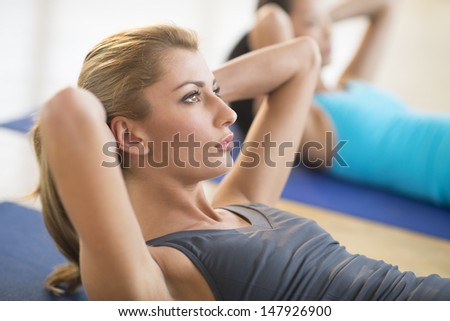Close-up of beautiful young woman doing sit-ups at gym with female friend in background