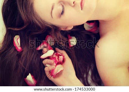 Close-up of beautiful young woman face with long blond hair and rose-petal - stock photo