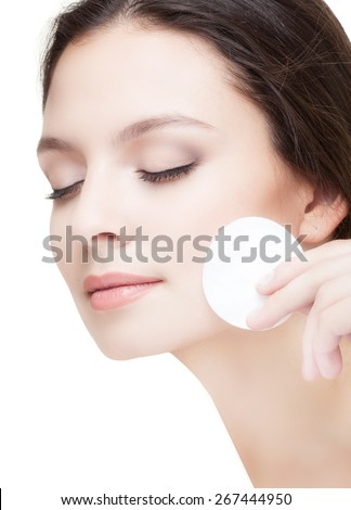 Close-up of Beautiful Young Woman Washing her Face with the Cotton Pad on the White Background. Eyes are Closed. - stock photo