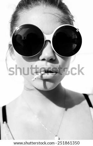 Close-up of beauty girl in trendy sunglasses  with cigarette. Toned black and white. White background, not isolated - stock photo