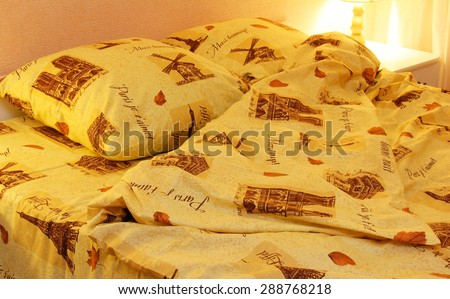 Close up of bedding sheets and pillow on bed and lamp