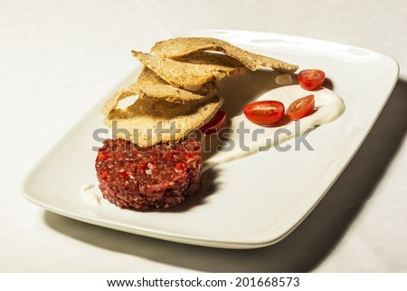 Close up of beef tartar with small toasts. on the plate