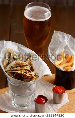 Close-up of beer snacks, sprat and french fries with gravy and glass of beer on wooden table - stock photo