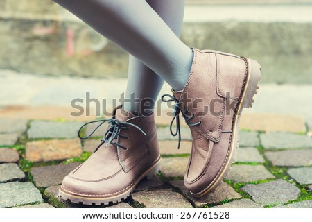 Close up of beige boots on child's feet - stock photo