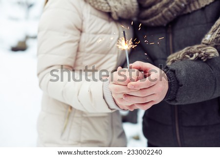Close-up of Bengal light in hands of lovers - stock photo