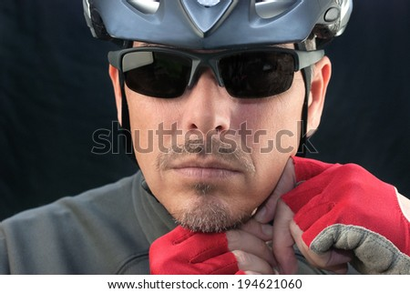 Close-up of bicycle courier putting on helmet. - stock photo