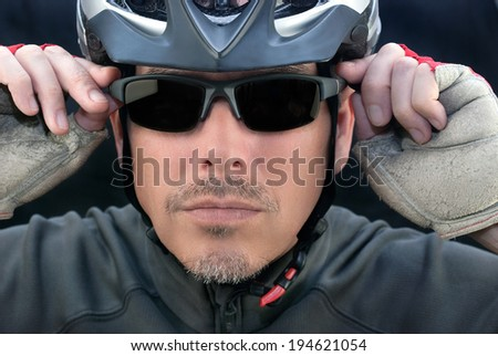 Close-up of bicycle courier putting on his sunglasses. - stock photo