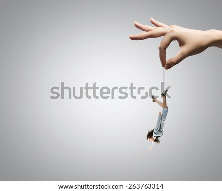 Close up of big human hand catching businesswoman - stock photo