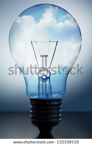 Close up of big light bulb standing with bright blue sky with clouds in it - stock photo