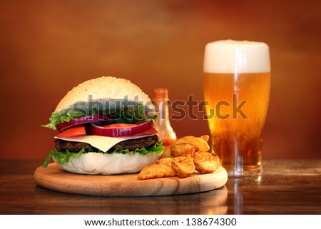 Close up of big tasty burger, french fries and beer - stock photo