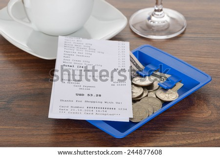 Close-up Of Bill And Currency On Wooden Table - stock photo